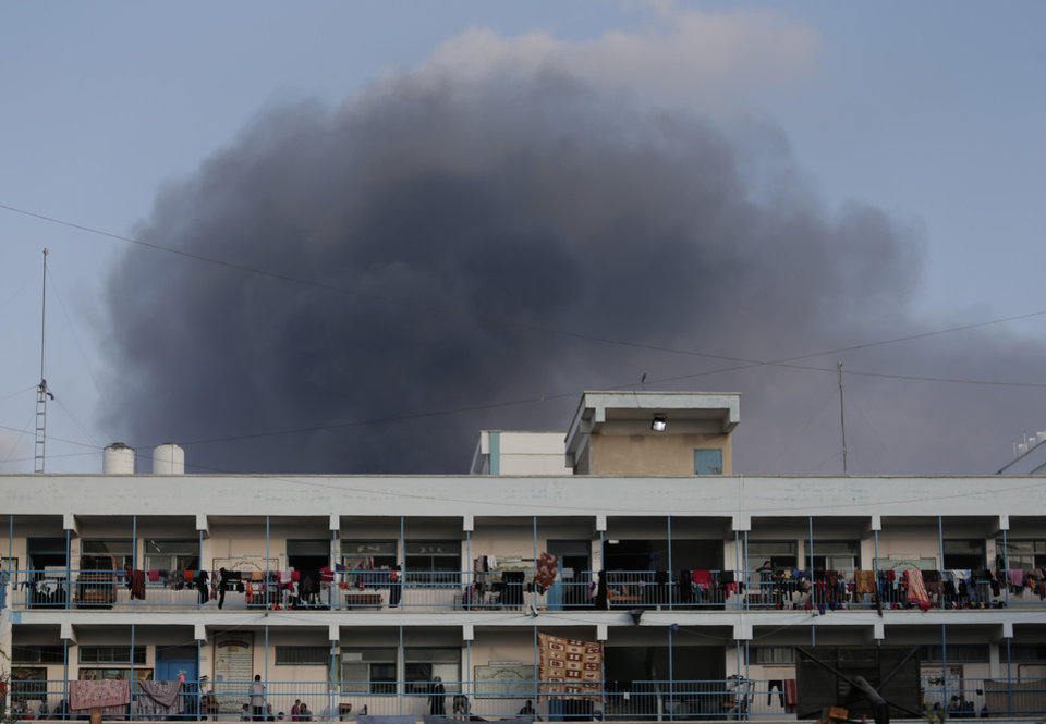 Photo - Smoke from the explosion of an Israeli strike rises over a U.N. school at Jebaliya refugee camp, in the northern Gaza Strip, where  Palestinian displaced people had found refuge, on Tuesday, July 29, 2014. The school is one of dozens of emergency shelters for those who have fled the fighting. About 180,000 Palestinians_about 10 percent of the entire population of Gaza_are seeking shelter in over 80 UNRWA schools, according to United Nations' Office for the Coordination of Humanitarian Affairs' July 28 report. (AP Photo/Lefteris Pitarakis)
