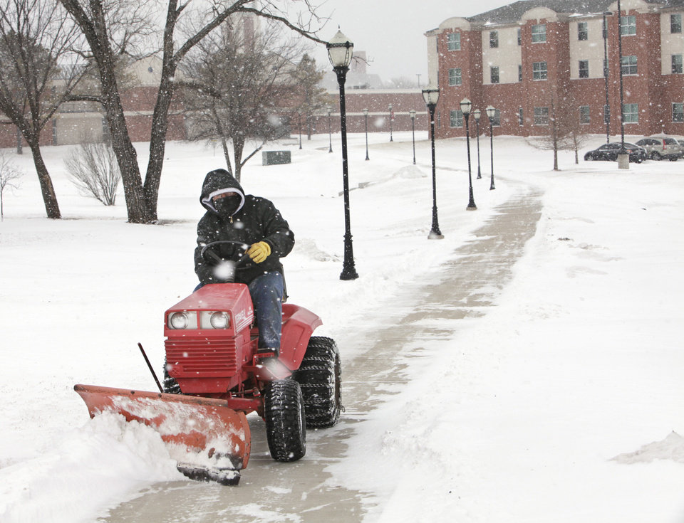Photo - Oklahoma Christian University maintenance worker  Mike Howard, 48, says he missed out on last week's blizzard because he was on a medical mission trip to Haiti where it was 90 degrees. Howard was making up for it Wednesday morning, plowing campus sidewalks in single-digit temperatures, Wednesday, February 9 , 2011. Photo by David McDaniel, The Oklahoman
