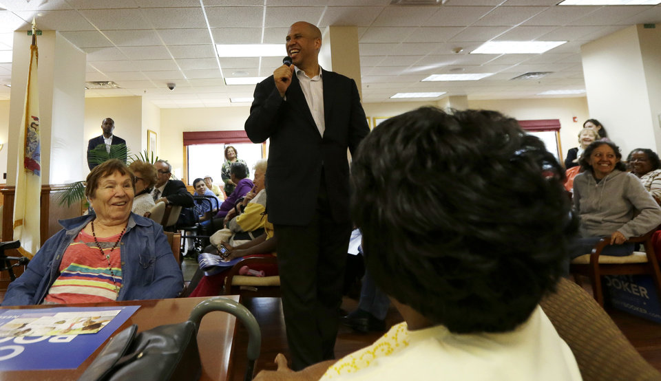 Photo - Newark Mayor Cory Booker, center, laughs while talking to supporters at a senior center, Tuesday, Oct. 15, 2013, in Newark, N.J. Booker will be going up against his Republican opponent Steve Lonegan Wednesday, Oct. 16, during a special election to fill New Jersey's vacant seat in the U.S. Senate. (AP Photo/Julio Cortez)