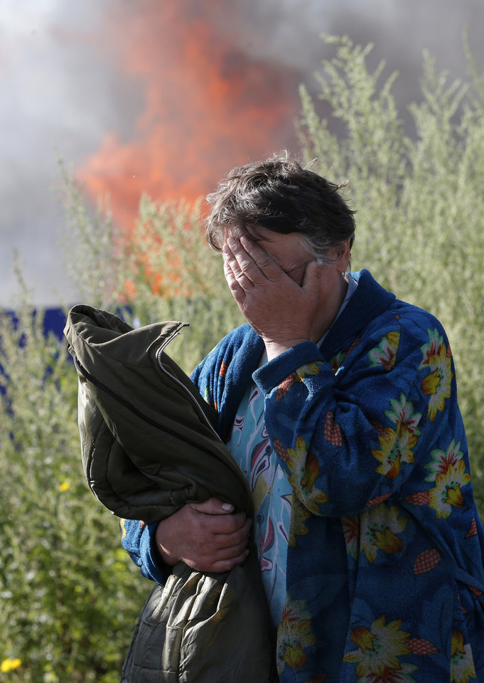 Photo - A woman cries near her burning house after shelling in the city of Slovyansk, Donetsk Region, eastern Ukraine, Monday, June 30, 2014. Residential areas came under shelling on Monday morning from government forces. (AP Photo/Dmitry Lovetsky)