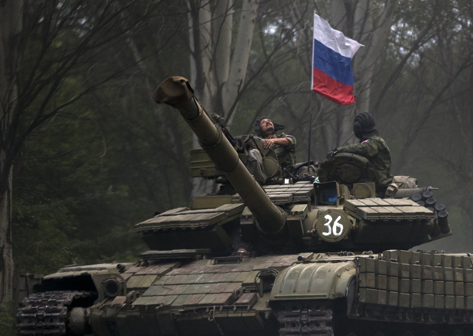 Photo - A pro-Russian rebel looks up while ridding on a tank flying Russia's flag, on a road east of Donetsk, Monday, July 21, 2014. Another 21 bodies have been found in the sprawling fields of east Ukraine where Malaysia Airlines Flight 17 was downed last week, killing all 298 people aboard. International indignation over the incident has grown as investigators still only have limited access to the crash site and it remains unclear when and where the victims' bodies will be transported. (AP Photo/Vadim Ghirda)