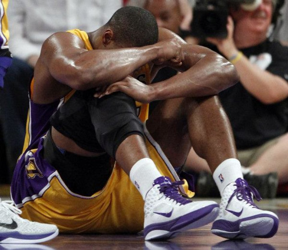 Los Angeles Lakers' Andrew Bynum holds his knee on the floor after being hurt during the first half of a NBA basketball game against the San Antonio Spurs in Los Angeles, Tuesday, April 12, 2011. Bynum hyperextended his right knee. (AP Photo/Chris Carlson) <strong>Chris Carlson</strong>