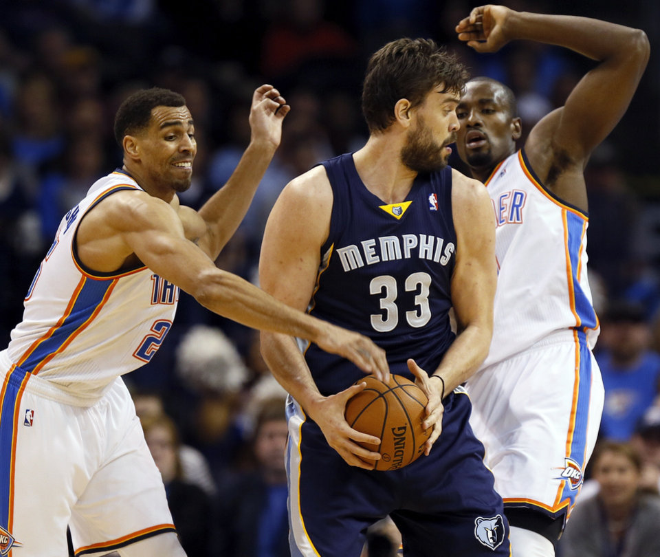 Oklahoma City\'s Thabo Sefolosha (25), left, and Serge Ibaka (9) defend Memphis\' Marc Gasol (33) during an NBA basketball game between the Memphis Grizzlies and the Oklahoma City Thunder at Chesapeake Energy Arena in Oklahoma City, Friday, Feb. 28, 2014. Photo by Nate Billings, The Oklahoman