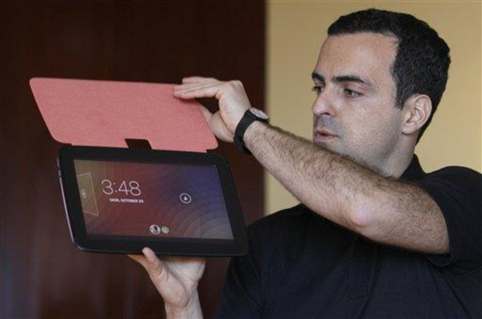 Hugo Barra, Android at Google Director of Product Management, holds up the Nexus 10 tablet at a Google announcement in San Francisco, Monday, Oct. 29, 2012. The tablet computer is without a doubt the gift of the year. just like it was last year. But if you resisted the urge in 2011, now is the time to give in. This season's tablets are better all around. Intense competition has kept prices very low, making tablets incredible values compared to smartphones and PCs  (AP Photo/Jeff Chiu)