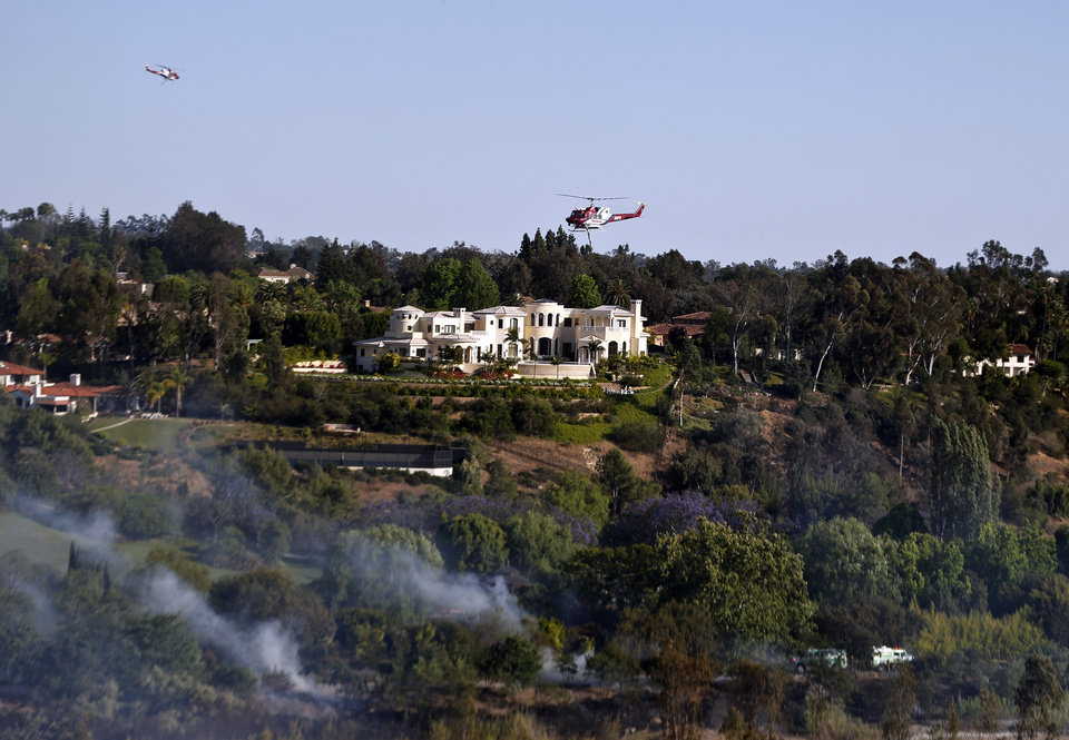 Photo - Smoke rises as firefighters work in the brush as two fire fighting helicopters pass  each other above one of the colossal homes of Fairbanks Ranch where a wild fire threatened homes Tuesday, May 13, 2014, in San Diego.  (Wildfires pushed by gusty winds chewed through canyons parched by California's drought, prompting evacuation orders for more than 20,000 homes on the outskirts of San Diego and another 1,200 homes and businesses in Santa Barbara County 250 miles to the north.  (AP Photo)