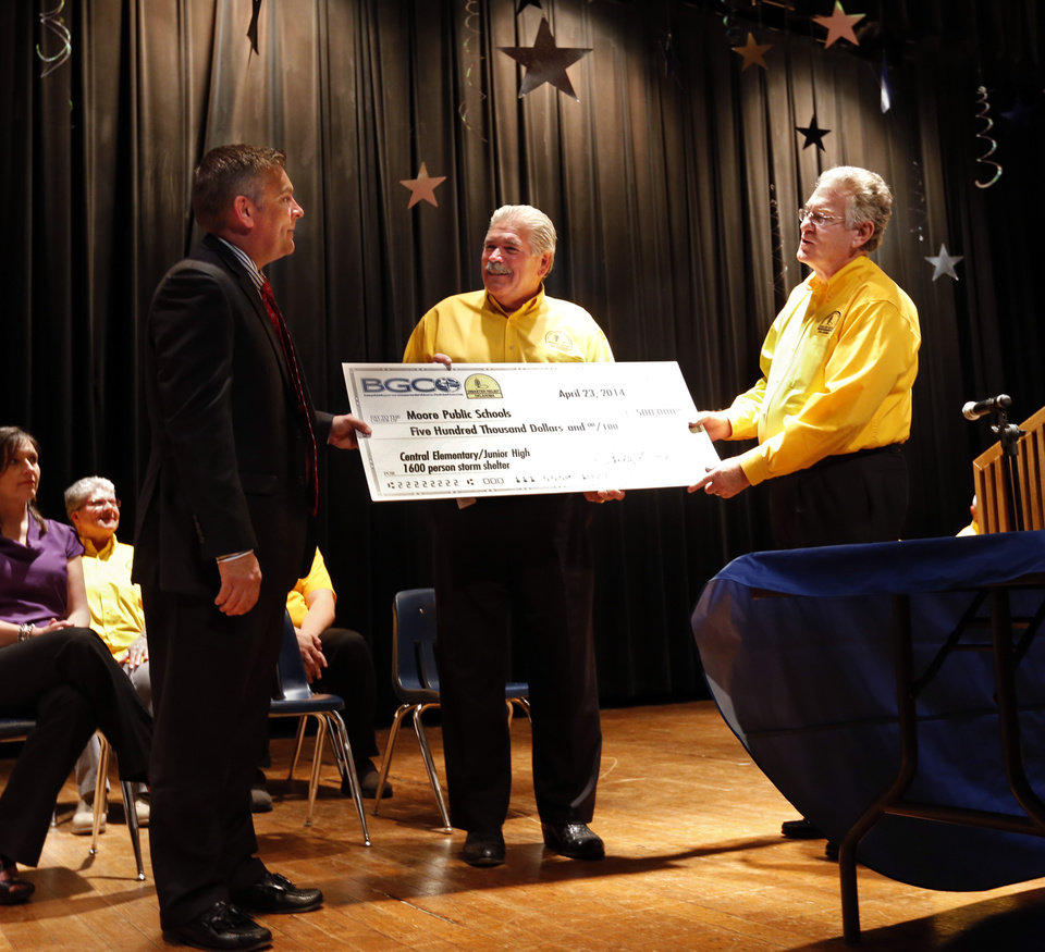 Photo - Moore Public Schools Superintendent Dr. Robert Romines accepts a ceremonial check from Baptist General Convention of Oklahoma executive director Dr. Anthony Jordan, right,  and Sam Porter, disaster relief director, as they announce a gift from the Baptist General Convention of $500,000 to Moore Public Schools for construction of a storm shelter on Wednesday, April 23, 2014 in Moore, Okla.  Photo by Steve Sisney, The Oklahoman