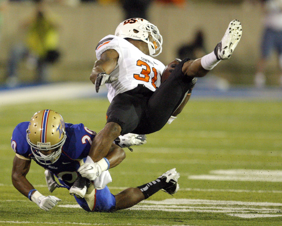Oklahoma State\'s\' Jeremy Smith (31) is brought down by Tulsa\'s Marco Nelson (20) during a college football game between the Oklahoma State University Cowboys and the University of Tulsa Golden Hurricane at H.A. Chapman Stadium in Tulsa, Okla., Sunday, Sept. 18, 2011. Photo by Sarah Phipps, The Oklahoman