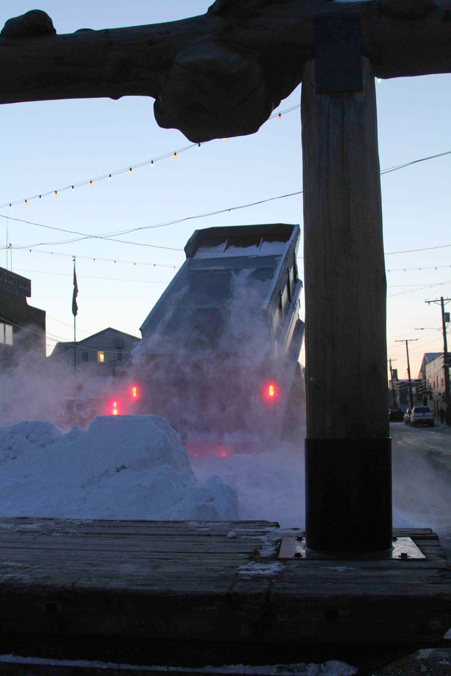Photo - A Nome public works truck dumps a load of snow onto Front Street on Sunday, March 9, 2014, in Nome, Alaska. The snow was trucked in to provide a trail for mushers to the finish line of the Iditarod Trail Sled Dog Race. The wooden frame is the famed burled arch finish line. (AP Photo/Mark Thiessen)