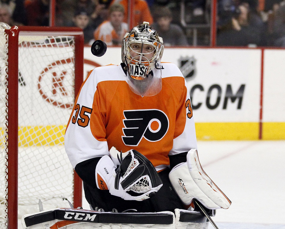 Photo - Philadelphia Flyers' Steve Mason watches the puck fly past during the first period of an NHL hockey game against the Buffalo Sabres, Sunday, April 6, 2014, in Philadelphia. (AP Photo/Tom Mihalek)