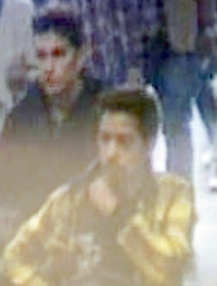 Photo - The image of two Iranian who Inetrpol say were traveling with stolen passports on a missing Malaysia Arlines jetliner displayed on a screen during a presser at the Interpol headquarters in Lyon, central France, Tuesday, March 11, 2014.  (AP Photo/Laurent Cipriani)