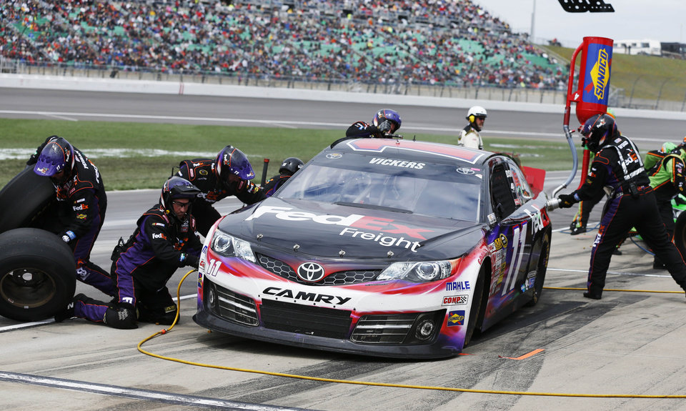 Photo - Brian Vickers (11) pits during a NASCAR Sprint Cup series auto race at Kansas Speedway in Kansas City, Kan., Sunday, April 21, 2013. (AP Photo/Orlin Wagner)