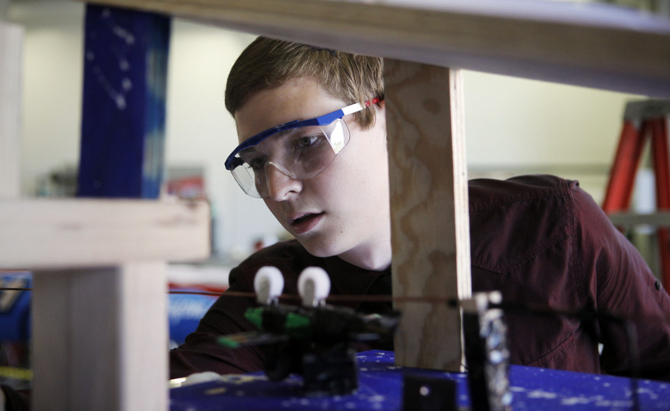 Sean English, 19, of Oklahoma City, sets up his contraption which would go through a number of processes to finally hammer a nail in a competition held Tuesday. Photo by K.T. KING, The Oklahoman <strong>KT King</strong>