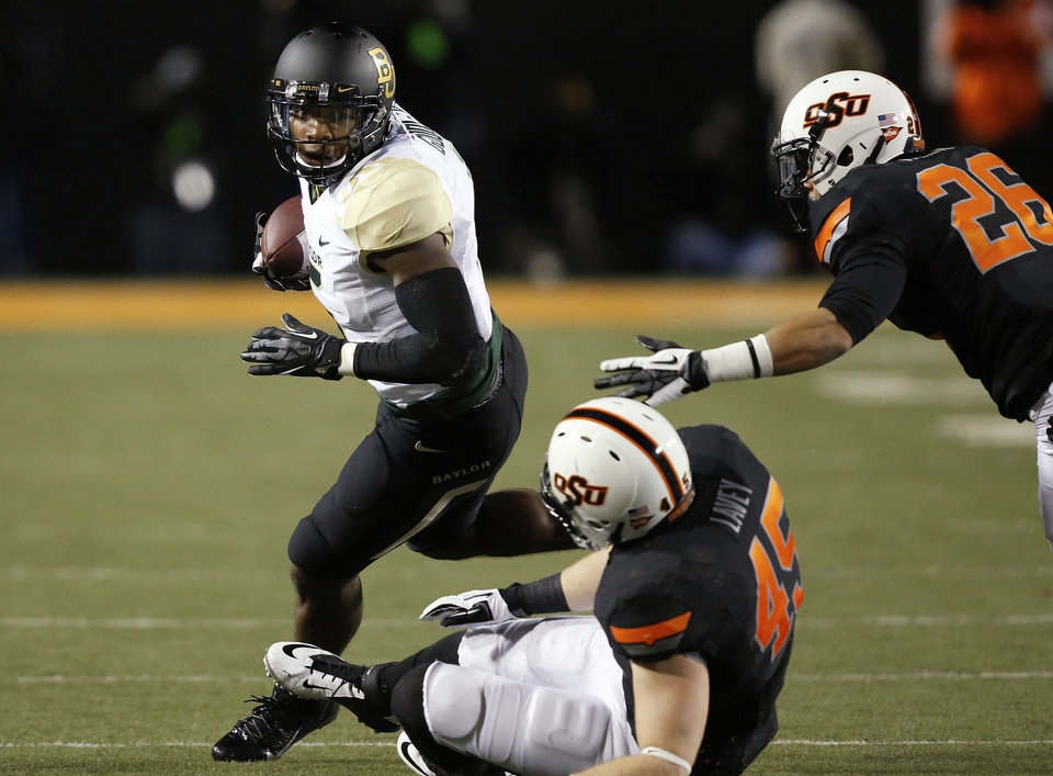 Photo - Baylor wide receiver Antwan Goodley (5) carries the ball past Oklahoma State defenders Caleb Lavey (45) and Tyler Patmon (26) in the first quarter of an NCAA college football game in Stillwater, Okla., Saturday, Nov. 23, 2013. (AP Photo/Sue Ogrocki)