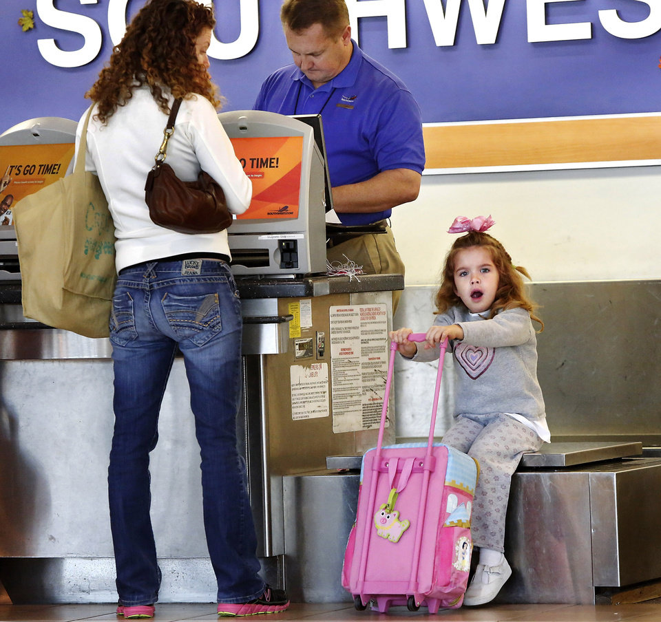 Madilynn, 5 1/2, holds the handle of her suitcase while sitting on the scales at the Southwest Airlines ticket counter, waiting for her mom, Amanda, of Oklahoma City, to take care of arrangements with the ticketing agent that will allow Madilynn to fly by herself for a visit with relatives. This is Madilynn's first time to fly alone, her mother said. Will Rogers World Airport was prepared for the onslaught of holiday travelers who converged there Wednesday, Nov. 21, 2012, in advance of the Thanksgiving holiday. Several thousand air travelers were expected to fly in and out of Oklahoma City's commercial airport. Photo by Jim Beckel, The Oklahoman