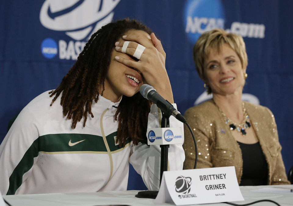Photo - Baylor's Brittney Griner, left, covers her face  during a news conference as head coach Kim Mulkey watches following their second-round game against Florida State  in the women's NCAA college basketball tournament Tuesday, March 26, 2013, in Waco, Texas. Griner had been asked how she felt being the second most important person in the arena during the game that former President George W. Bush attended. Baylor won 85-47. (AP Photo/Tony Gutierrez)
