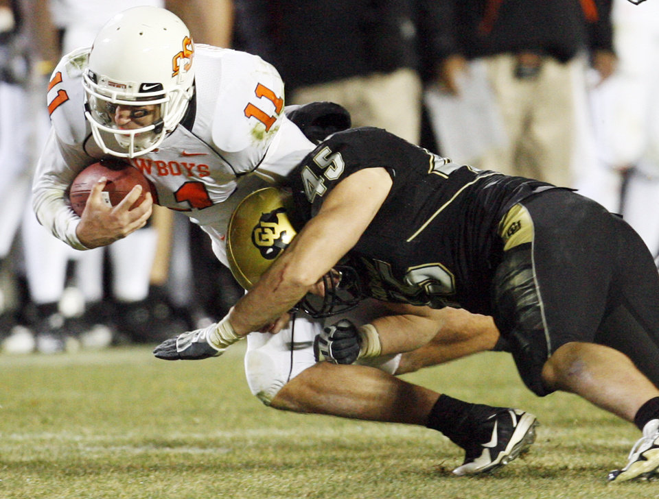 Photo - OSU's Zac Robinson (11) is taken down by Jeff Smart (45) of Colorado after running for a first down in the fourth quarter during the college football game between Oklahoma State University and University of Colorado at Folsom Field in Boulder, Colo., Saturday, Nov. 15, 2008. OSU won, 30-17. BY NATE BILLINGS, THE OKLAHOMAN