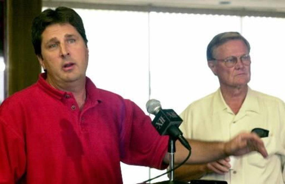 Photo - 2002 file photo - Texas Tech football coach Mike Leach, left, and Texas Tech athletic director  Gerald  Myers, right, hold a joint news conference in Lubbock, Texas, July 10, 2002, to discuss questions about the football program's $400,000 deficit. (AP Photo/Lubbock Avalanche-Journal, Jim Watkins)