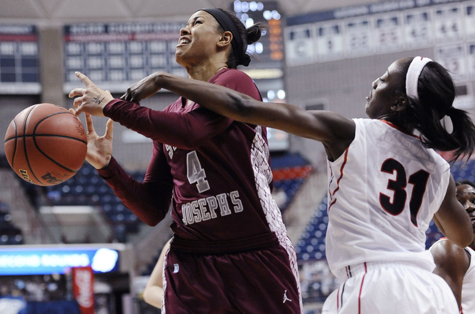 Photo - Georgia's Erika Ford, right, fouls Saint Joseph's Natasha Cloud, left, during the first half of a first-round game of the NCAA women's college basketball tournament, Sunday, March 23, 2014, in Storrs, Conn. (AP Photo/Jessica Hill)