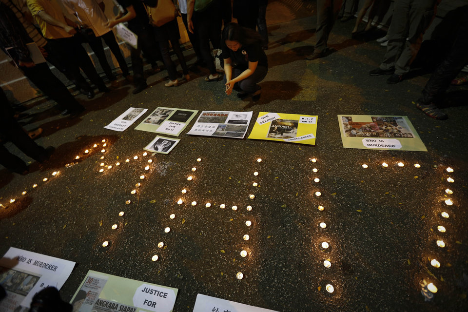 Photo - A woman looks at newspaper cuttings at a candlelight vigil for the victims of Malaysia Airlines Flight 17 in Kuala Lumpur, Malaysia, Saturday, July 19, 2014. Malaysian Transport Minister Liow Tiong Lai said the country is