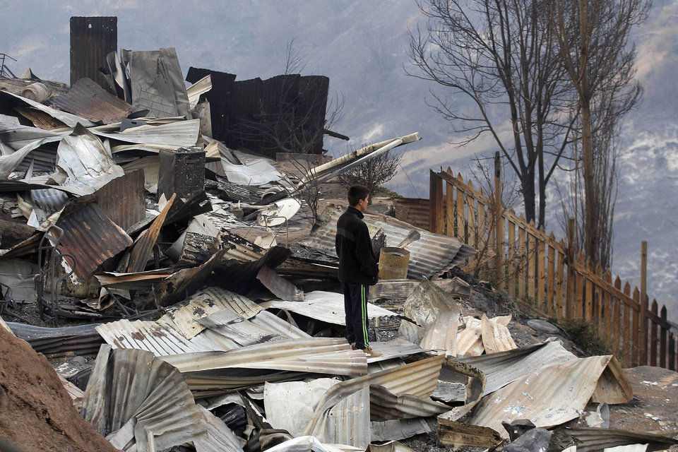 Photo - A man stands over and looks at the charred remains of homes after a large forest fire reached urban areas in Valparaiso, Chile, Sunday April 13, 2014. Authorities say the fires have destroyed hundreds of homes, forced the evacuation of thousands and claimed the lives of at least seven people.  ( AP Photo/ Luis Hidalgo)