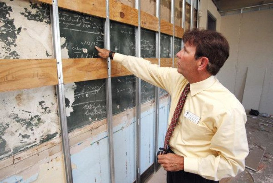 Norman School District Assistant Superintendent Roger Brown points to a 1935 date on a blackboard at Longfellow Middle School. The blackboard will be preserved for future use. PHOTO BY STEVE SISNEY, THE OKLAHOMAN STEVE SISNEY - THE OKLAHOMAN
