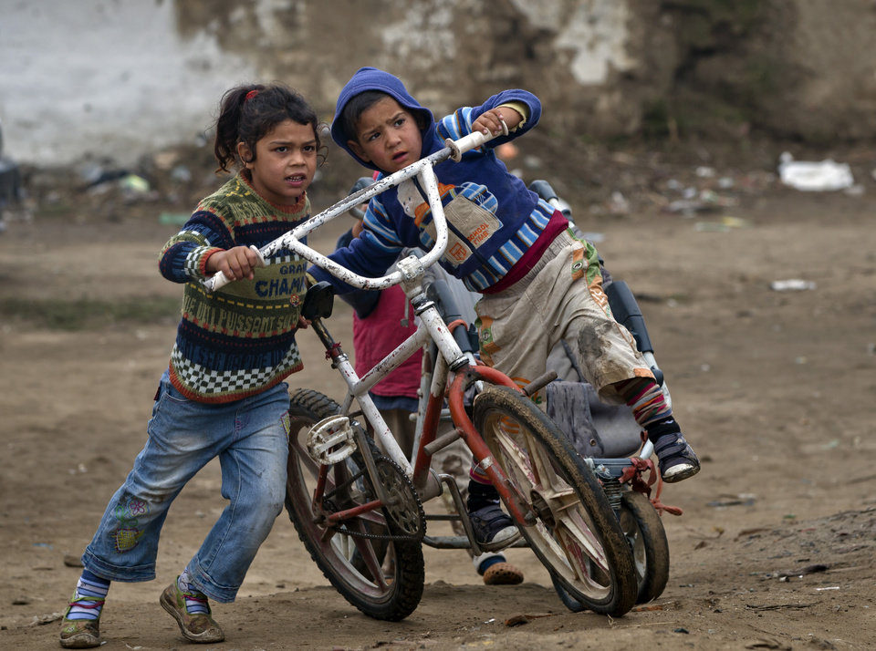 Photo - Bulgarian Roma children play with bicycles  in a Roma neighborhood of Nikolaevo, Bulgaria, Friday, Oct. 25, 2013. Sasha Ruseva, a Bulgarian Roma woman from this town, is under investigation by Bulgarian authorities trying to find out  if she is the mother of a suspected abduction victim in neighboring Greece known as