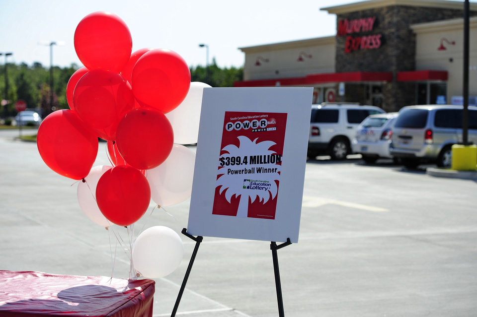 Photo - Balloons and a sign announcing a winner of the Powerball drawing are set up in front of Murphy Express store on Thursday, Sept. 19, 2013  in Lexington, S.C.  A $400 million winning ticket in the latest Powerball drawing was sold at the service station just off I-20 west of Columbia, officials with the South Carolina Education Lottery said Thursday.  Winners in South Carolina do not have to come forward publicly but Lottery Executive Director Paula Harper Bethea noted that, in order to claim the winnings, the ticketholder must contact state lottery officials within 180 days.  (AP Photo/ Richard Shiro)
