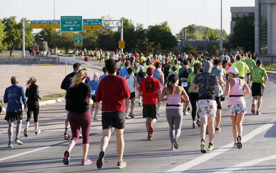 Photo - Runners travel north on Lincoln Blvd. around the state Capitol during the Oklahoma City Memorial Marathon in Oklahoma City, Sunday, April 28, 2019. [Nate Billings/The Oklahoman]