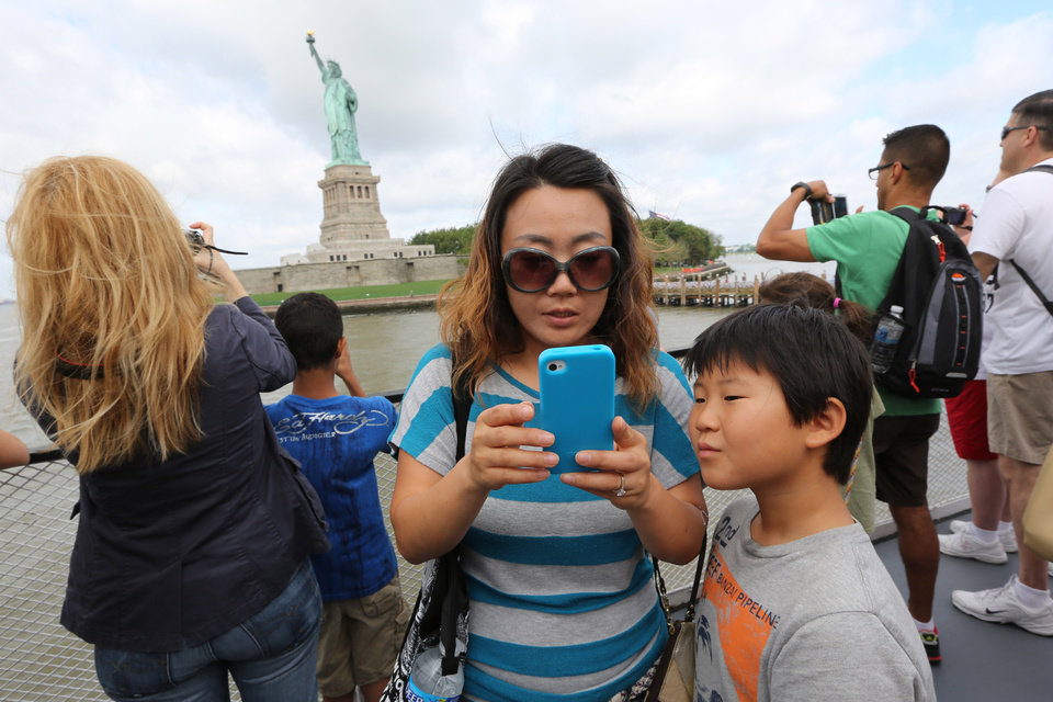 Photo - Visitors to fhe Statue of Liberty take photos as they arrive on the first tourist ferry to leave Manhattan, Thursday, July 4, 2013 at  in New York. The Statue of Liberty finally reopened on the Fourth of July months after Superstorm Sandy swamped its little island in New York Harbor as Americans across the country marked the holiday with fireworks and barbecues. (AP Photo/Mary Altaffer)