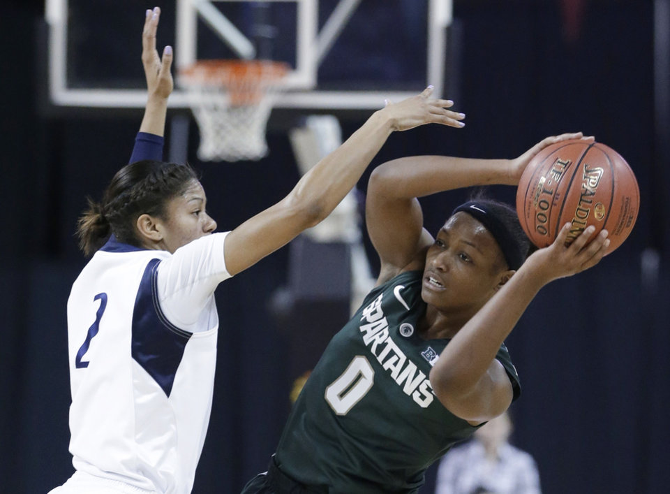 Photo - Michigan State guard Kiana Johnson, right, looks to pass against Penn State guard Dara Taylor during the first half of an NCAA college basketball game in the Big Ten women's tournament in Hoffman Estates, Ill., on Saturday, March 9, 2013. (AP Photo/Nam Y. Huh)