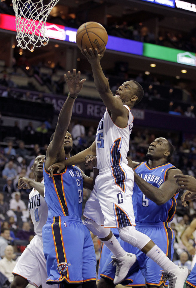 Charlotte Bobcats' Kemba Walker (15) gets to the basket past Oklahoma City Thunder's Kevin Durant (35) and Kendrick Perkins (5) during the first half of an NBA basketball game in Charlotte, N.C., Friday, March 8, 2013. (AP Photo/Bob Leverone) ORG XMIT: NCBL102