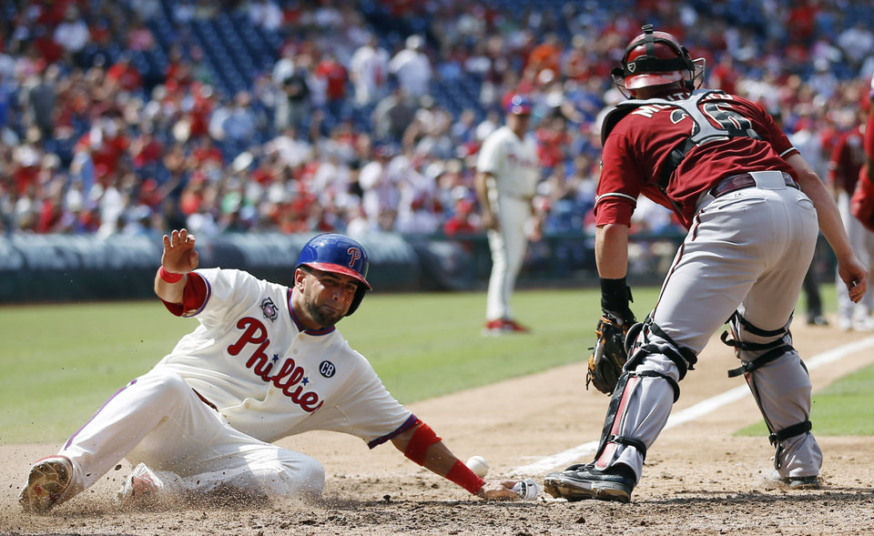Photo - Philadelphia Phillies' Wil Nieves, left, scores past Arizona Diamondbacks catcher Miguel Montero on a hit by Ben Revere during the seventh inning of a baseball game, Sunday, July 27, 2014, in Philadelphia. Revere reached third after a fielding error by left fielder David Peralta on the play. Philadelphia won 4-2. (AP Photo/Matt Slocum)