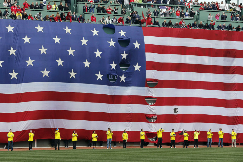Boston Marathon volunteers stand beneath a giant flag on the outfield wall during a tribute to victims of the Boston Marathon bombings, before a baseball game between the Boston Red Sox and the Kansas City Royals in Boston, Saturday, April 20, 2013. (AP Photo/Michael Dwyer) ORG XMIT: MAMD127