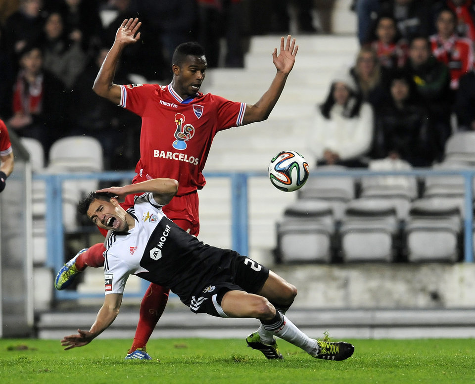 Photo - Benfica's is Nico Gaitan, foreground, from Argentina falls on the penalty box after a tackle by Gil Vicente's Armindo 'Brito' Furtado, from Cape Verde, in a Portuguese League soccer match at the Cidade de Barcelos stadium, in Barcelos, northern Portugal, Saturday, Feb. 1, 2014. (AP Photo/Paulo Duarte)