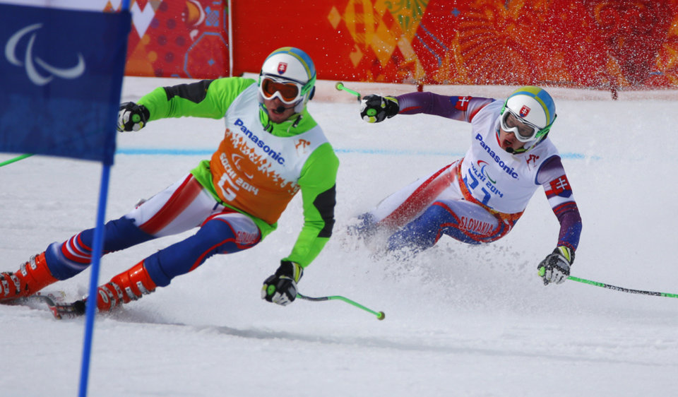 Photo - Miroslav Haraus of Slovakia, right, and his guide Maros Hudik race to win 2nd place in the men's downhill, visually impaired event at the 2014 Winter Paralympic, Saturday, March 8, 2014, in Krasnaya Polyana, Russia. (AP Photo/Dmitry Lovetsky)
