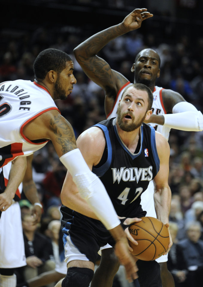 Photo -   Minnesota Timberwolves' Kevin Love (42) looks to shoot against Portland Trail Blazers' J.J. Hickson, back, and LaMarcus Aldridge, left, during the first half of an NBA basketball game in Portland, Ore., Friday, Nov. 23, 2012. (AP Photo/Greg Wahl-Stephens)
