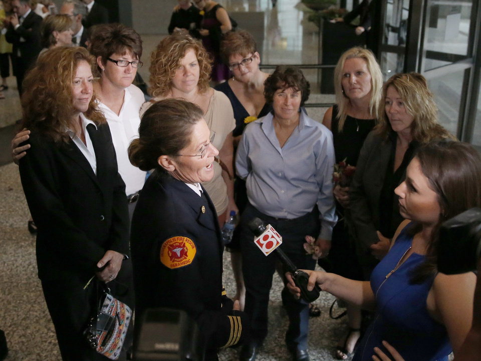 Photo - Ruth Morrison, center, a retired Indianapolis Fire Department battalion chief, talks to a reporter after attending a hearing before the 7th U.S. Circuit Court of Appeals on the challenges to Indiana and Wisconsin's gay marriage ban Tuesday, Aug. 26, 2014, in Chicago. Morrison worries that because Indiana won't recognize the woman she married in another state as her wife, she wouldn't be able to pass on pension and other benefits if she dies. (AP Photo/Charles Rex Arbogast)