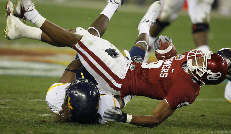 Photo - Oklahoma's Juaquin Iglesias (9) is up ended by the West Virginia defensa during the second half of the Fiesta Bowl college football game between the University of Oklahoma Sooners (OU) and the West Virginia University Mountaineers (WVU) at The University of Phoenix Stadium on Wednesday, Jan. 2, 2008, in Glendale, Ariz. 