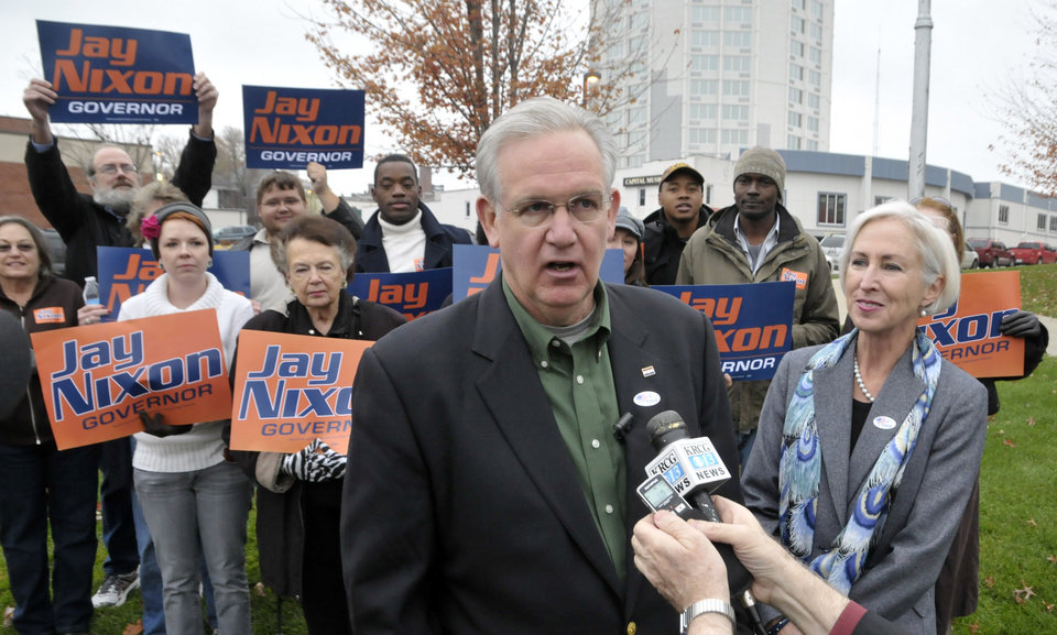 Photo -   Missouri Gov. Jay Nixon and first lady Georganne Nixon, at right, pause for a brief interview Tuesday morning, Nov. 6, 2012, after casting their ballots in Jefferson City, Mo. Supporters were waiting for them as they arrived to vote. Nixon faces Republican Dave Spence in the gubernatorial race. (AP Photo/Jefferson City News-Tribune, Julie Smith)