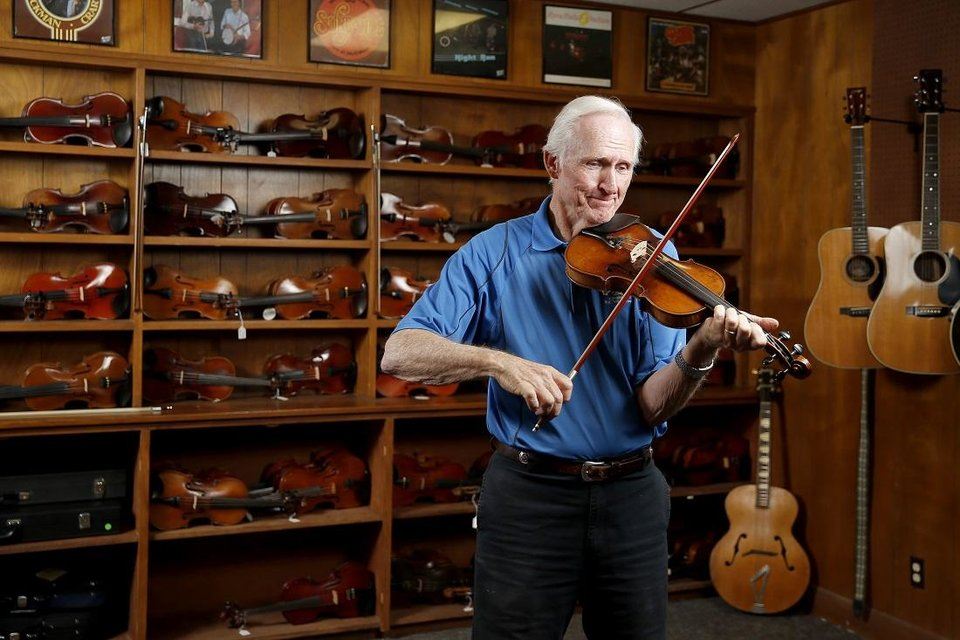 Photo - Byron Berline plays inside his Double Stop Fiddle Shop in Guthrie, Okla., Friday, July 5, 2019. [Bryan Terry/The Oklahoman Archives]