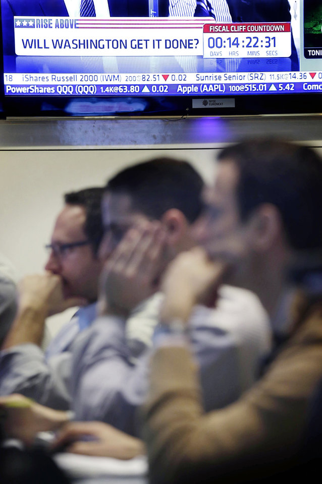 Photo - A television news show talks about the fiscal cliff while traders work on the floor at the New York Stock Exchange in New York, Monday, Dec. 31, 2012. The stock market struggled for direction Monday morning after five days of losses, with the
