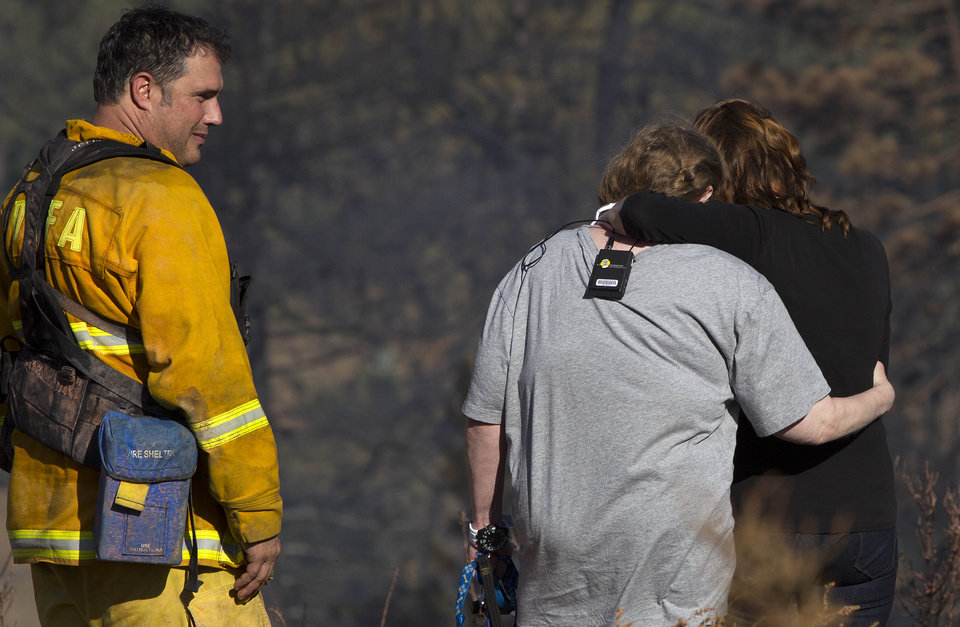 Photo - Anne Elizabeth, whose house was spared in a wildfire, hugs friend Maria Simas as Paul Thomas, volunteer firefighter with the Julian/Cuyamaca Fire Protection Service, looks on, Thursday, July 3, 2014, in the Julian, Calif, area. (AP Photo/UT San Diego, Sean M. Haffey)