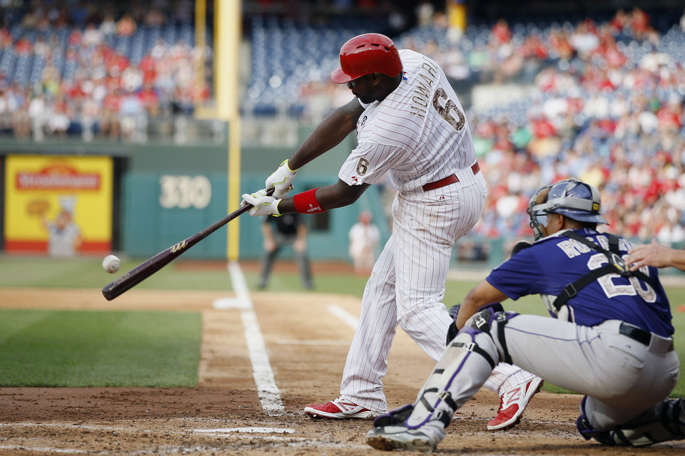 Philadelphia Phillies' Ryan Howard, left, hits an RBI-single off Colorado Rockies starting pitcher Jhoulys Chacin during the fourth inning of a baseball game, Monday, May 26, 2014, in Philadelphia. At right, is catcher Wilin Rosario. (AP Photo/Matt Slocum)
