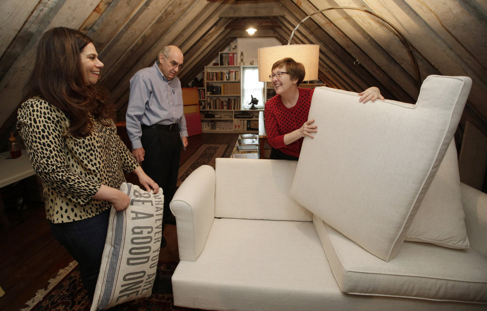 Photo - In this Sunday, Jan. 12, 2014, photo, Rebecca Gwynne, left, of Tuckahoe, N.Y., reacts as Marijane Hamren inspects Gwynne's Simplicity Sofa with her husband Jim Hamren, in Tuckahoe, N.Y.  While Simplicity's furniture is sold only over the Internet, some customers want to see and try out the sofas and chairs. Owner Jeff Frank contacts people who have already bought his furniture, and asks them if they'll let a prospective customer stop by to take a look. (AP Photo/Kathy Willens)