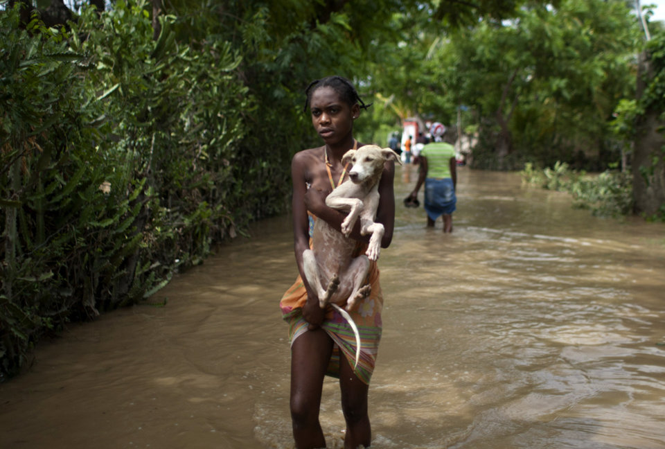 A young woman carries a dog on a flooded street after the passing of Tropical Storm Isaac in Port-au-Prince, Haiti, Sunday Aug. 26, 2012. The death toll in Haiti from Tropical Storm Isaac has climbed to seven after an initial report of four deaths, the Haitian government said Sunday. (AP Photo/Dieu Nalio Chery) ORG XMIT: PAP114