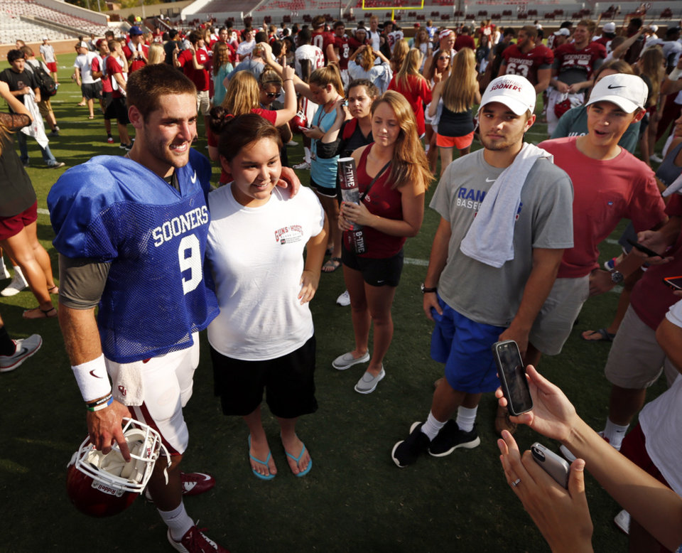 Photo - Quarterback Trevor Knight poses for a picture with Sheyenne Aimerson, Tahlequah, during the University of Oklahoma Sooners (OU) practice and Student Day at Gaylord Family-Oklahoma Memorial Stadium in Norman, Okla., on Thursday, Aug. 21, 2014. Photo by Steve Sisney, The Oklahoman
