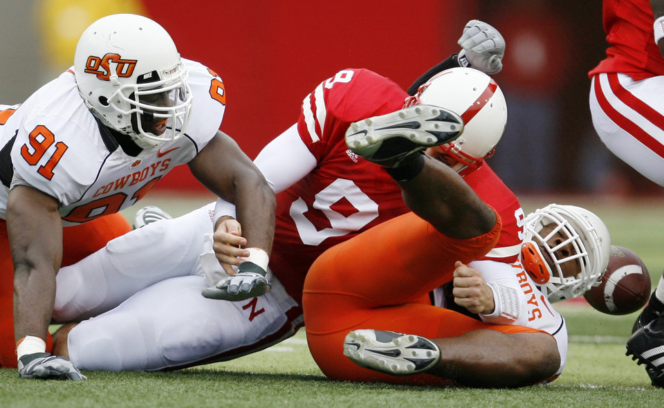 Photo - Udo Chinasa, left, and Donovon Woods bring down Sam Keller of Nebraska and cause a fumble during  the college football game between Oklahoma State University (OSU) and the University of Nebraska at Memorial Stadium in Lincoln, Neb., on Saturday, Oct. 13, 2007. By Bryan Terry, The Oklahoman