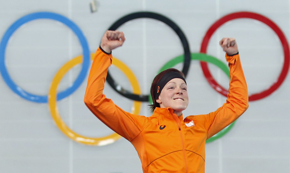 Photo - Gold medallist Jorien ter Mors of the Netherlands jumps in celebration during the flower ceremony for the women's 1,500-meter speedskating race at the Adler Arena Skating Center during the 2014 Winter Olympics in Sochi, Russia, Sunday, Feb. 16, 2014. (AP Photo/Pavel Golovkin)