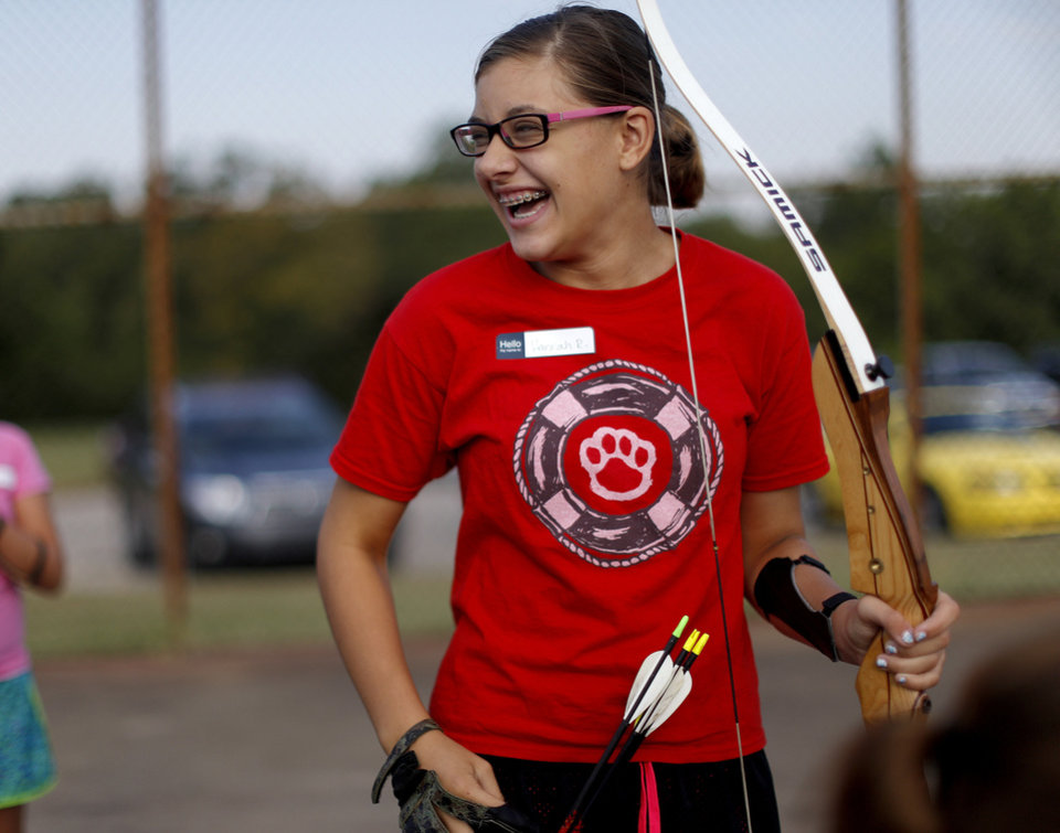 Photo - CHILD / CHILDREN / KIDS: Hannah Riel, 11, of Moore reacts after shooting during a Junior Olympic Archery Development Club shoot put on by the Trosper Archery Club on Saturday, August 24, 2013, at Trosper Park in Oklahoma City. This was Riel's first time shooting as she and over 60 participants, from beginners to intermediates, that took part in the shoot which takes place every Saturday. For $5 each person is supplied with equipment and instruction starting at 9am for beginners and 10am for intermediate shooters. Photo by Bryan Terry, The Oklahomane
