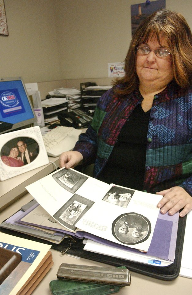 Photo - Linda Foster with a scrapbook of her grandfather, to the left is a photo of her and her grandfather and in the front is his Echo harmonica.  BY GARY CROW, FOR THE OKLAHOMAN                          ORG XMIT: KOD